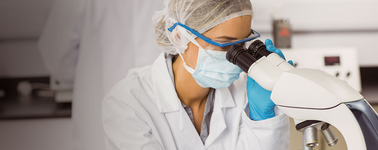Quality researcher using microscope in lab